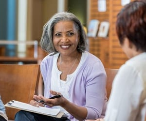 A hospice social worker smiles and reviews paperwork with a client during a conversation.