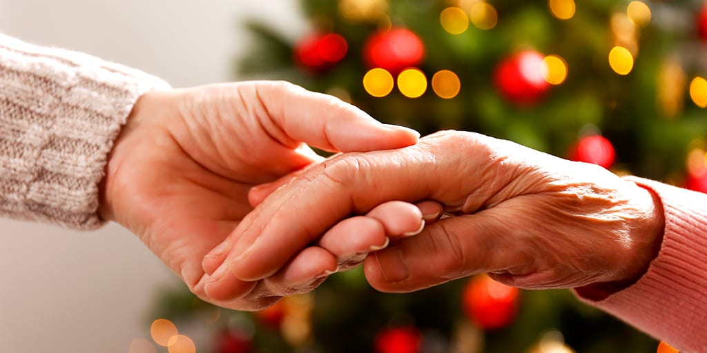 Caregiver and elderly hospice patient holding hands in front of Christmas tree